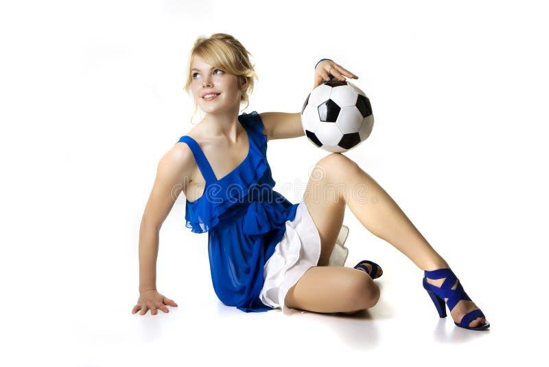 Blond meisje in een blauwe kleding met voetbalbal stock fotografie
