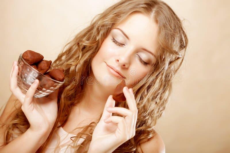 Blond meisje in handeling om een chocoladesuikergoed te eten royalty-vrije stock afbeelding