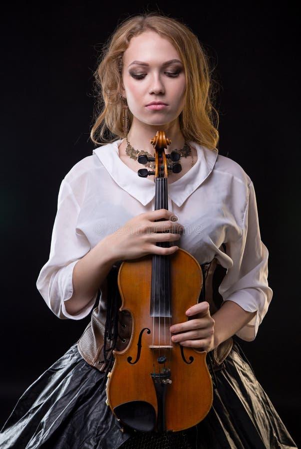 Blond meisje met de viool en neer het kijken stock afbeelding