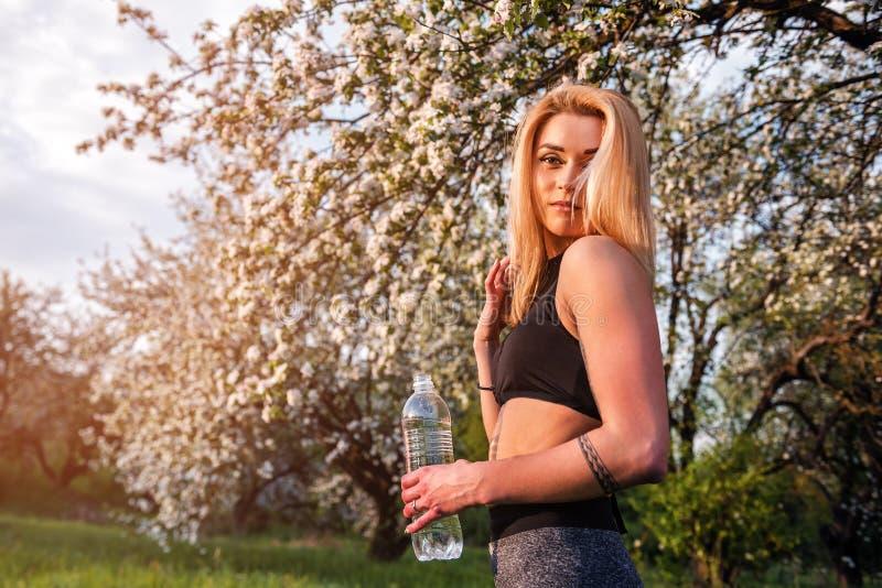 Blond meisje met fles water royalty-vrije stock afbeelding