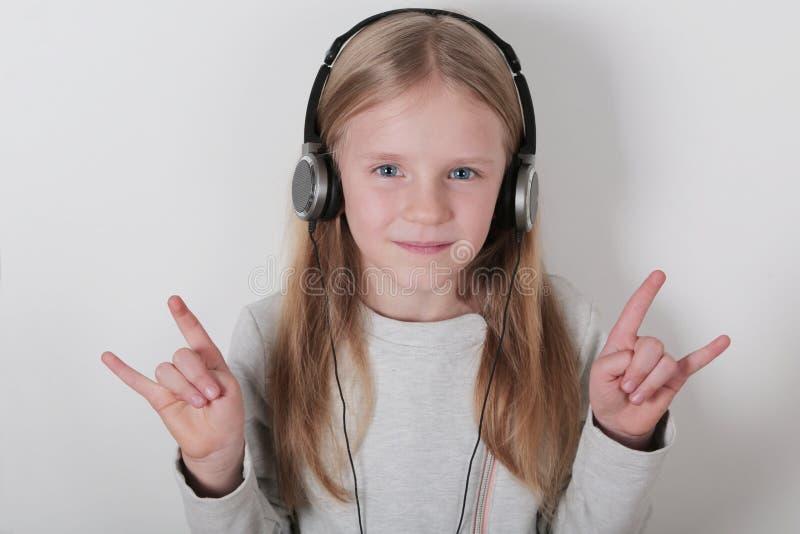 Blond meisje met hoofdtelefoons het luisteren muziek en het zingen Leuk meisje die een rots-n-broodje maken ondertekenen stock afbeeldingen