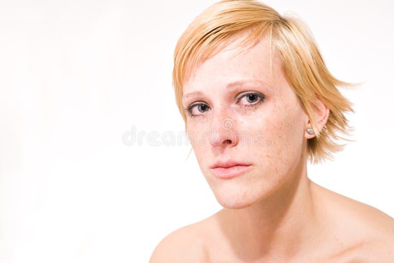 Blond meisje met kort haar dat droevig voelt stock foto