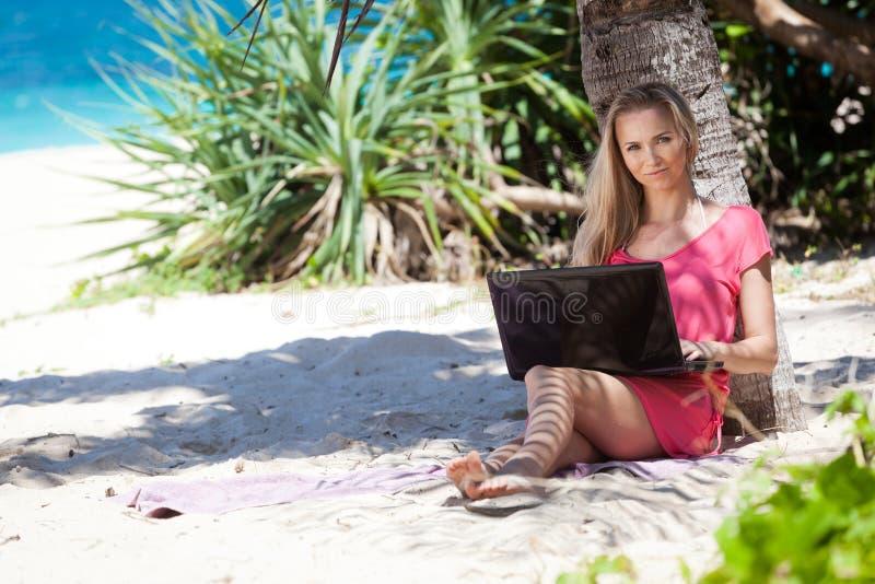 Blond meisje met laptop op tropisch strand stock foto's