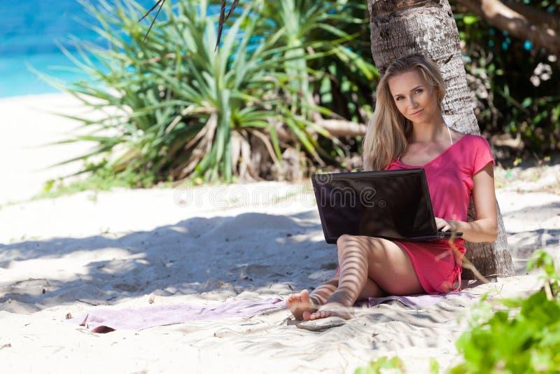 Blond meisje met laptop op tropisch strand stock foto