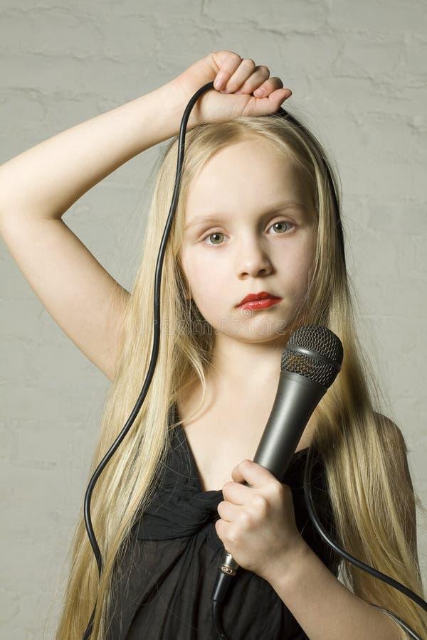 Blond meisje met microfoon stock foto