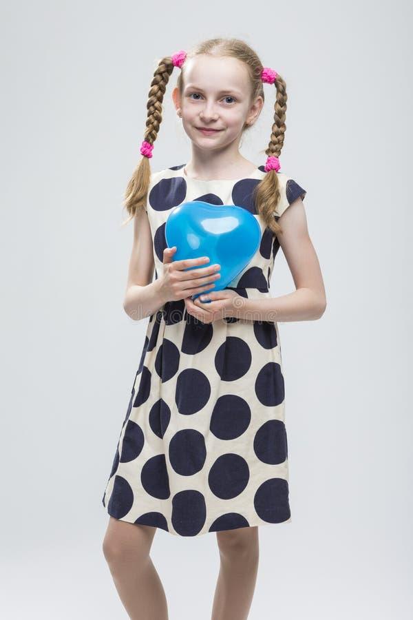 Blond Meisje met Vlechten die in Polka Dot Dress Against White stellen royalty-vrije stock afbeeldingen