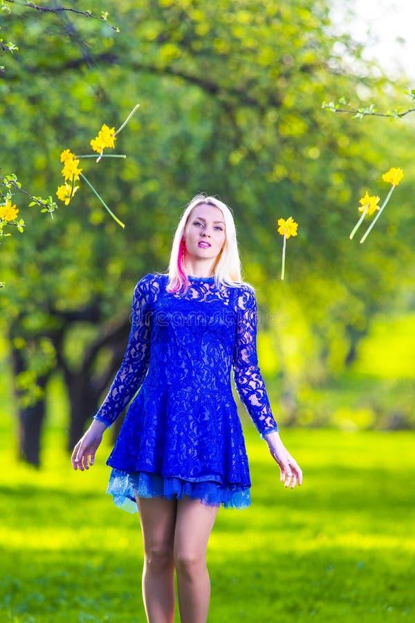 Blond Meisje voor Dalende Bos van Gele narcissen weg Het stellen tegen Aardachtergrond stock foto's