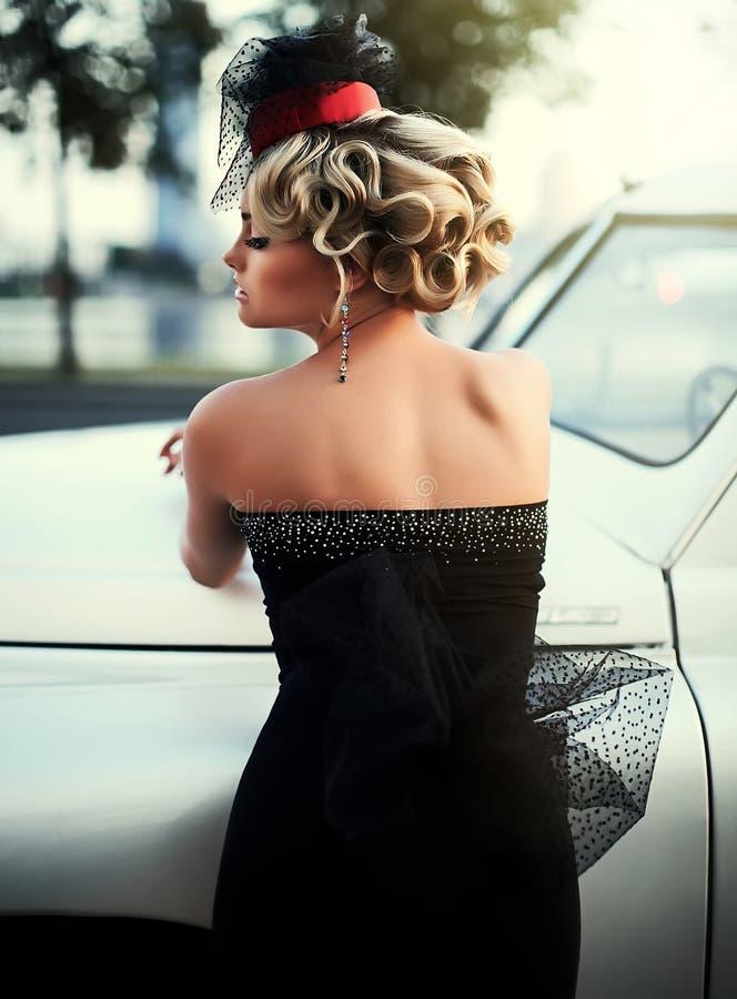 Blond meisjesmodel met heldere make-up en krullend kapsel in het retro stijl stellen dichtbij oude witte auto royalty-vrije stock afbeelding