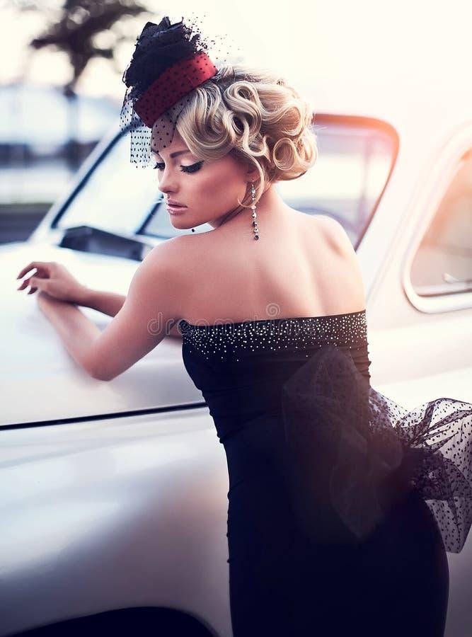 Blond meisjesmodel met heldere make-up en krullend kapsel in het retro stijl stellen dichtbij oude witte auto royalty-vrije stock foto's