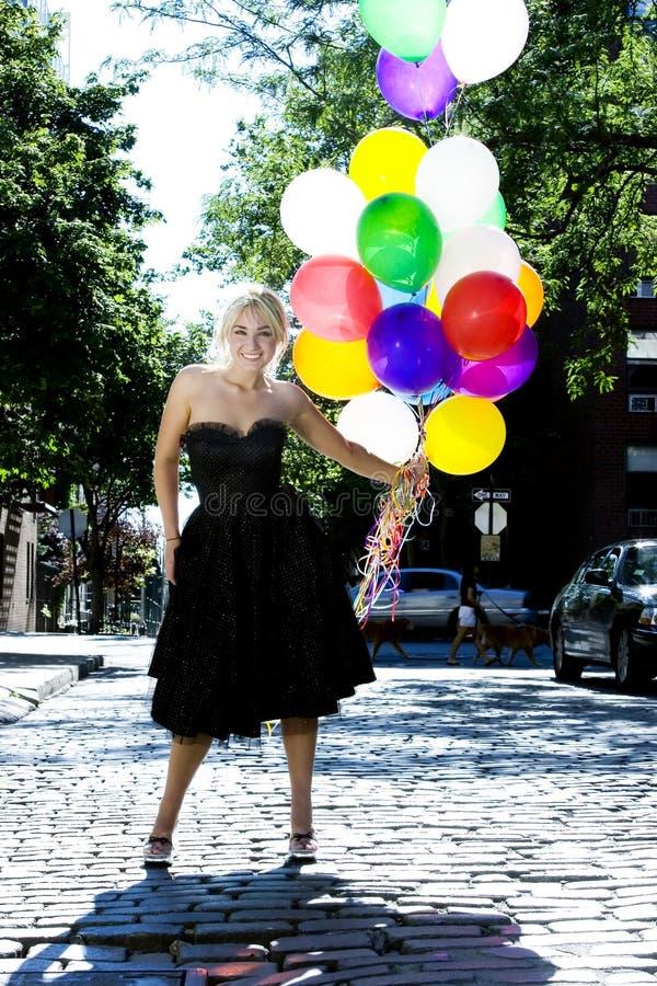 Blond met ballons uit in de zon royalty-vrije stock fotografie