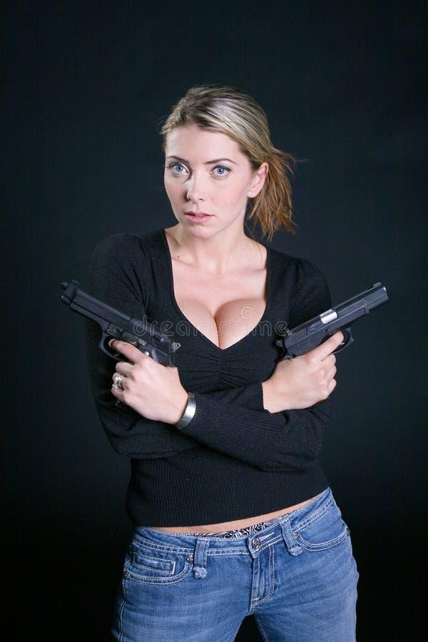 Blond met twee pistolen en een houding stock fotografie