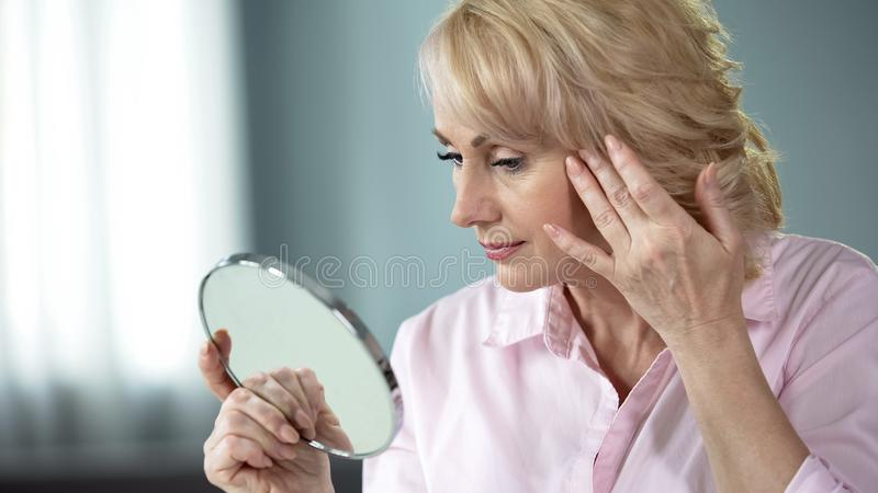 Blond middle-aged lady looking in mirror at her eye wrinkles, beauty injections. Stock photo royalty free stock image