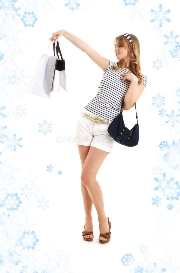 Blond mit Einkaufenbeuteln und -schneeflocken stockbild
