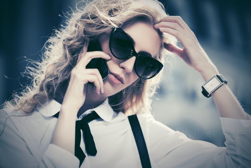 Blond modeaffärskvinna i solglasögon som kallar på mobiltelefonen på stadsgatan arkivbilder
