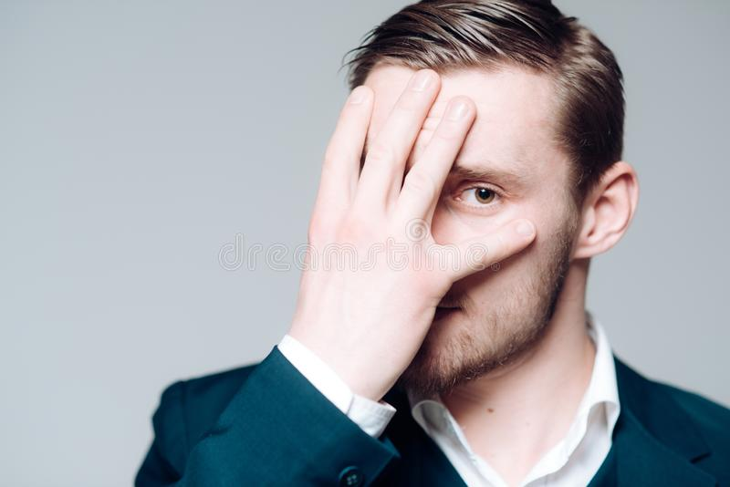Blond model isolated on gray background. Bearded guy with hazel eyes covering his face with palm royalty free stock images