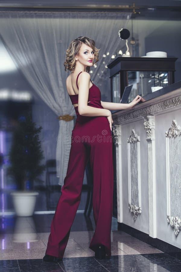 Blond modell för härlig kvinna i en röd jumpsuit en innegrej och arkivbild