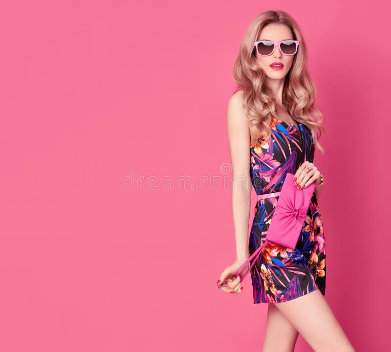 Blond modell för mode i sommarJumpsuit på rosa färger royaltyfria bilder