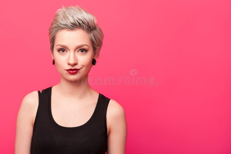 Blond modellflicka som ler över rosa bakgrund royaltyfri fotografi