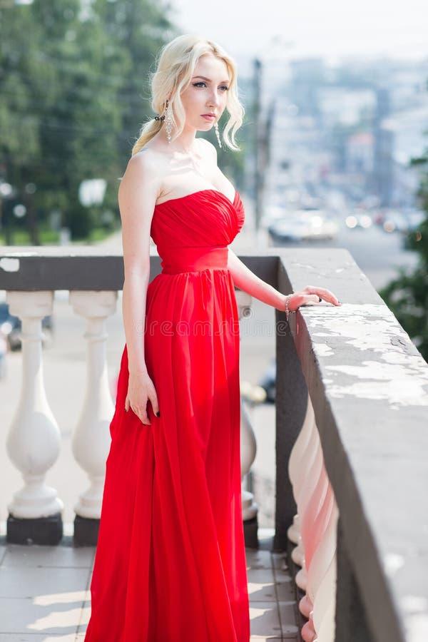 Blond modellkvinna för skönhet i röd klänning för afton royaltyfri foto