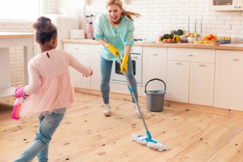 Blond moder som moppar golvet och dansar med dottern arkivfoto