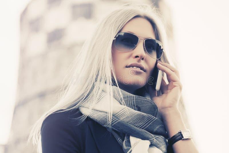 Blond-modezakenvrouw in een zonnebril die in de openlucht met een mobiele telefoon praat royalty-vrije stock afbeeldingen
