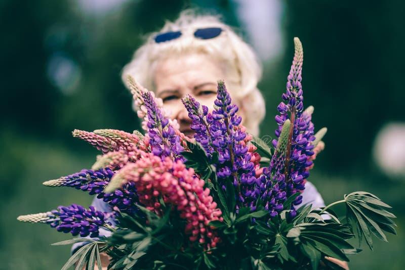 Blond mogen kraftig kvinna som rymmer en lupine bukett på naturbakgrund Begreppet av skönhet och kropprealiteten Solnedg?ngen t?n arkivfoto