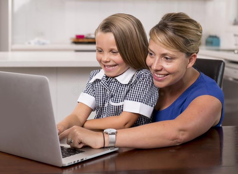 Blond mother woman together with her young beautiful and sweet little girl 6 to 8 years old sitting at home kitchen enjoying with royalty free stock image