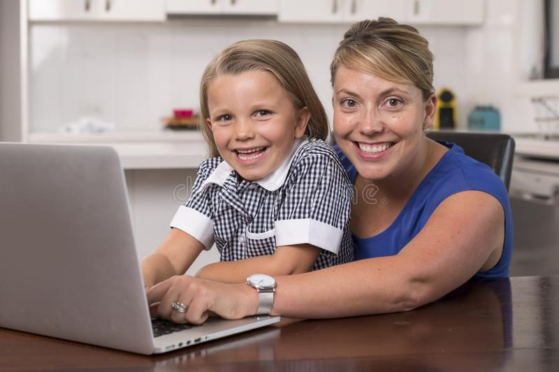 Blond mother woman together with her young beautiful and sweet little girl 6 to 8 years old sitting at home kitchen enjoying with royalty free stock photography