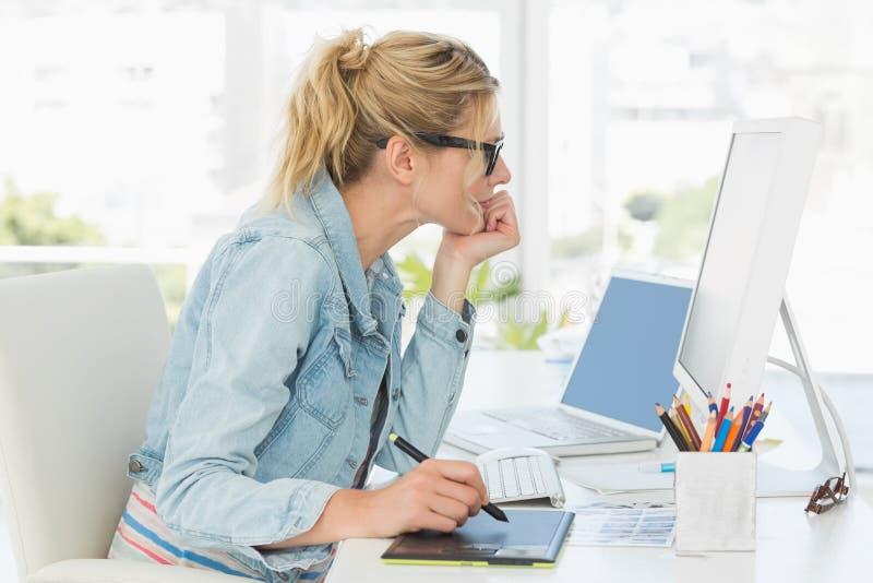 Blond nätt märkes- användande digitizer på hennes skrivbord royaltyfri bild