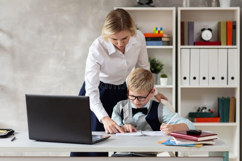 Blond nauczyciel sprawdza pracę domową jej młody uczeń w bluzce zdjęcia stock