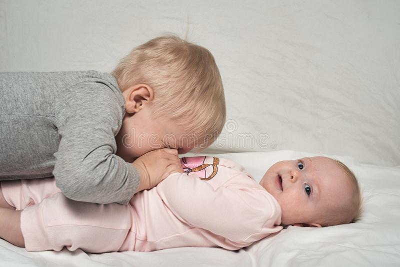 Blond older brother plays with his little sister. Child interaction royalty free stock photo