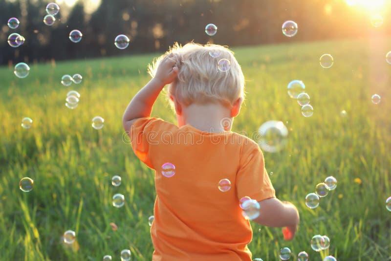 Blond pojke för gulligt litet barn som spelar med såpbubblor på sommarfält Lyckligt barnsommartidbegrepp Autentisk livsstilbild arkivbild