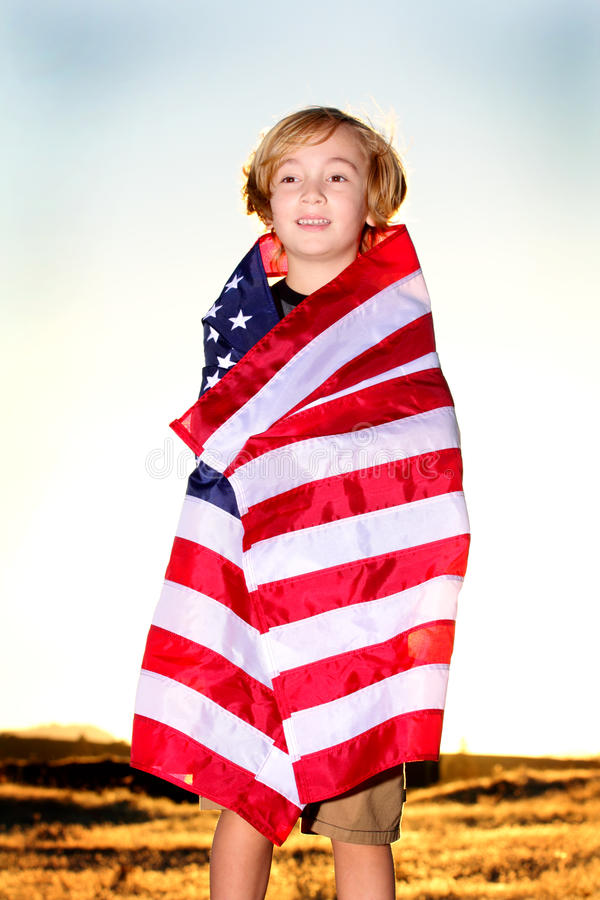 Blond pojke i amerikanska flaggan arkivbild
