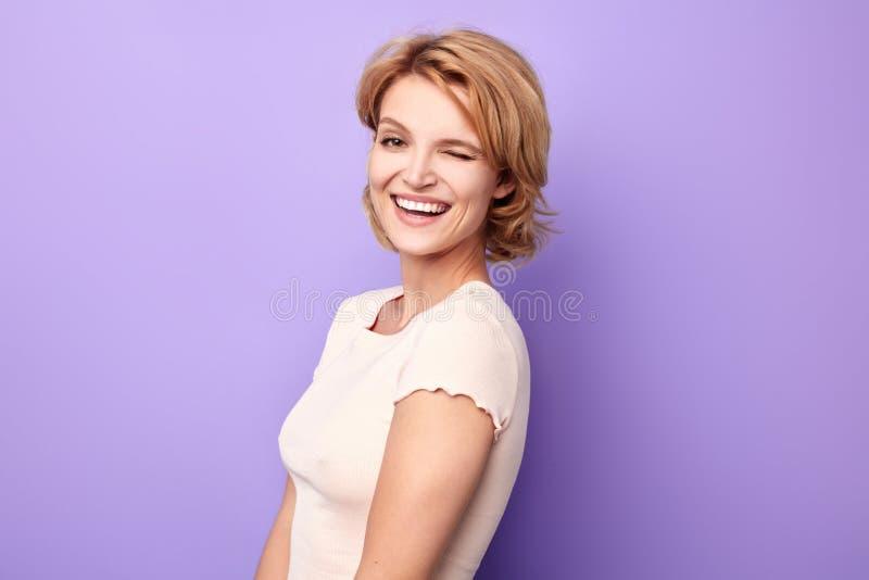 Blond positiv charmig listig kvinna som blinkar på kameran royaltyfria foton