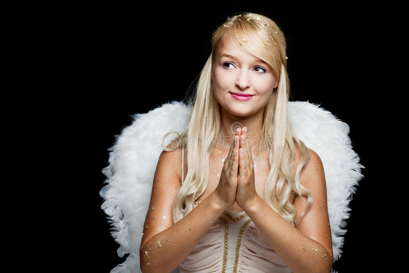 Blond praying angel with wings of white feathers. Blond angel with wings of white feathers, she's smiling and has her hands in a praying position royalty free stock photos