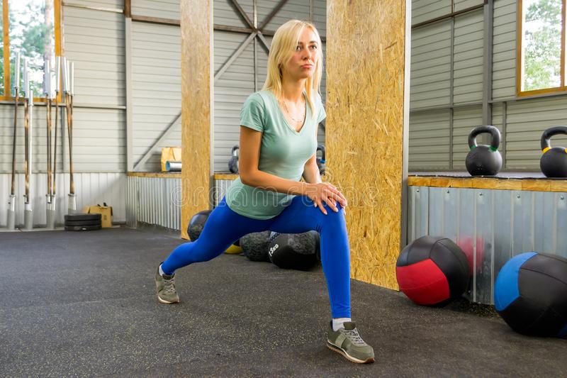 Blond pretty girl is doing stretching by lashes raising her leg royalty free stock images