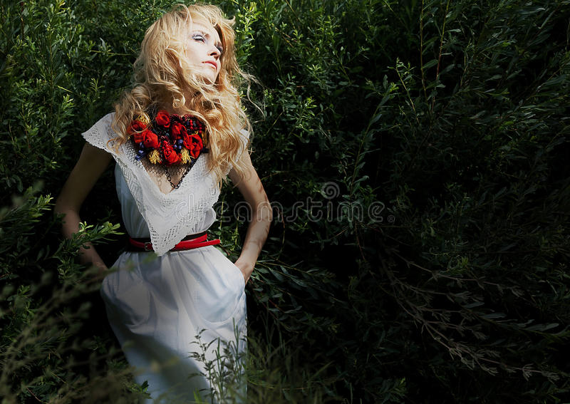 Blond pretty girl in green bushes dreaming stock photos