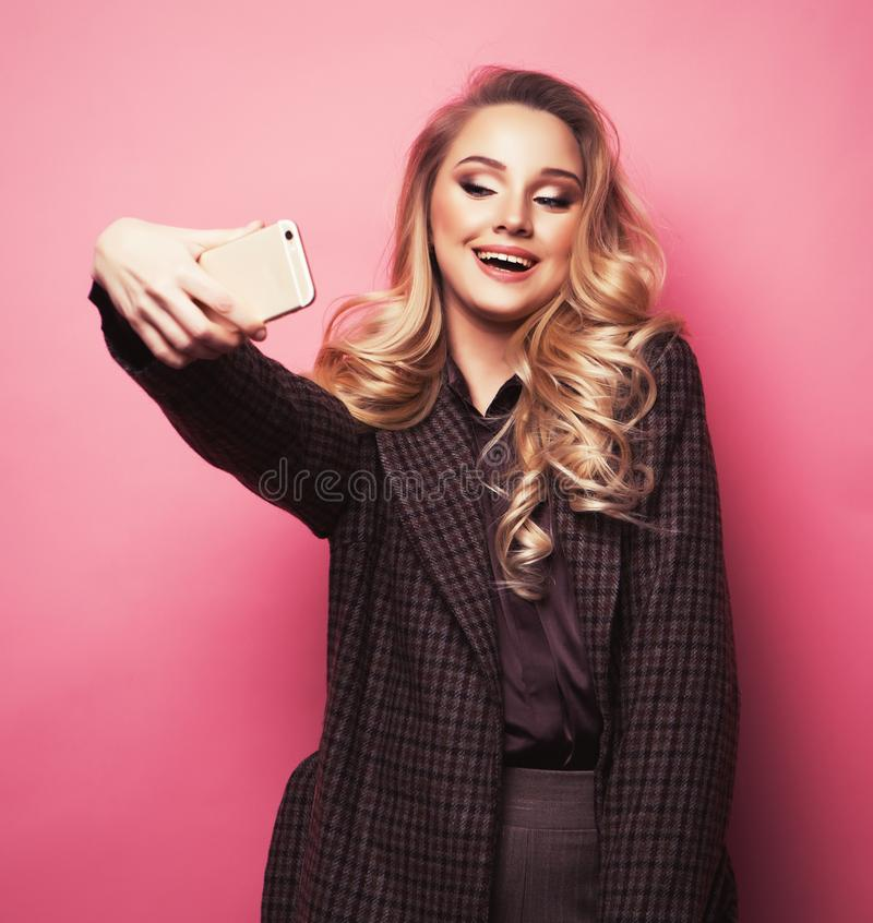 Blond pretty girl taking photo makes self portrait on smartphone over pink background royalty free stock image