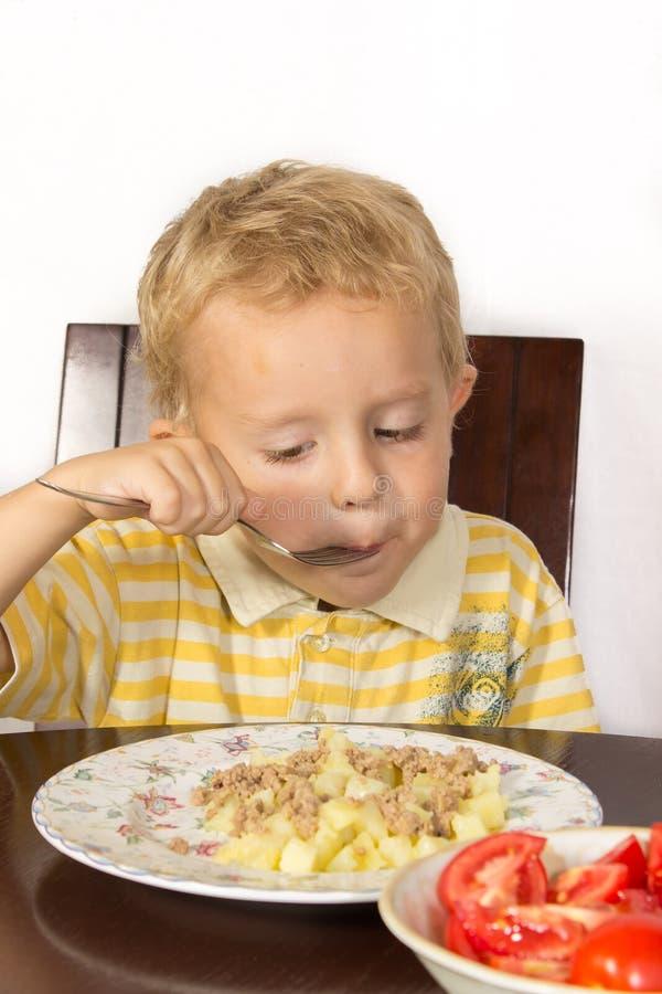 Blond pys som försöker att äta med potatisar för en gaffel med kött och tomater royaltyfri fotografi