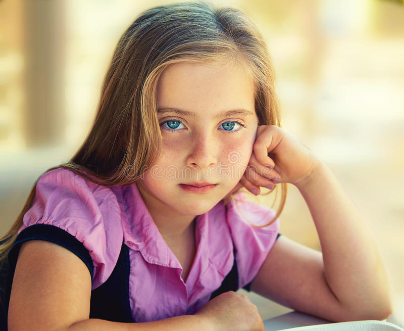 Blond relaxed sad kid girl expression blue eyes royalty free stock photography