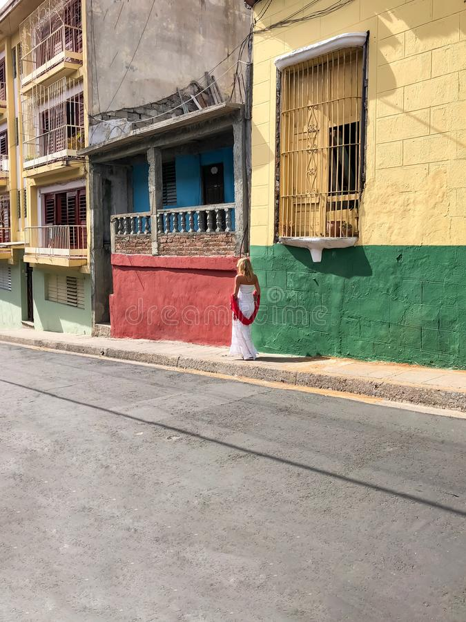 Blond resor i gatan med kulöra hus i Santiago de Cuba royaltyfri foto