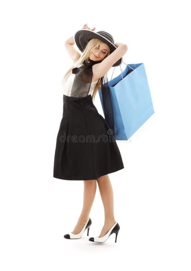 Blond in retro hoed met blauwe het winkelen zak royalty-vrije stock fotografie