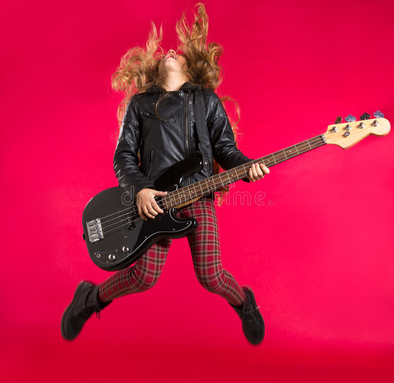 Blond Rock and roll girl with bass guitar jump on red royalty free stock images