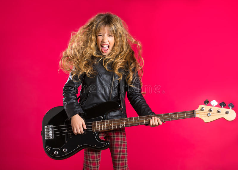 Blond Rock and roll girl with bass guitar on red stock images