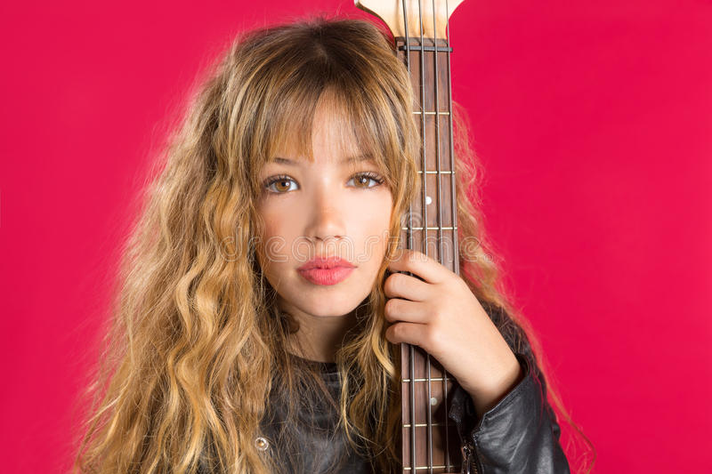 Blond Rock and roll girl with bass guitar on red stock photos