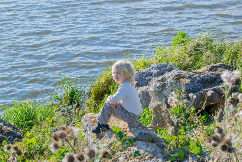 Blond rozważny chłopiec obsiadanie przy brzeg rzeki na skały obraz stock