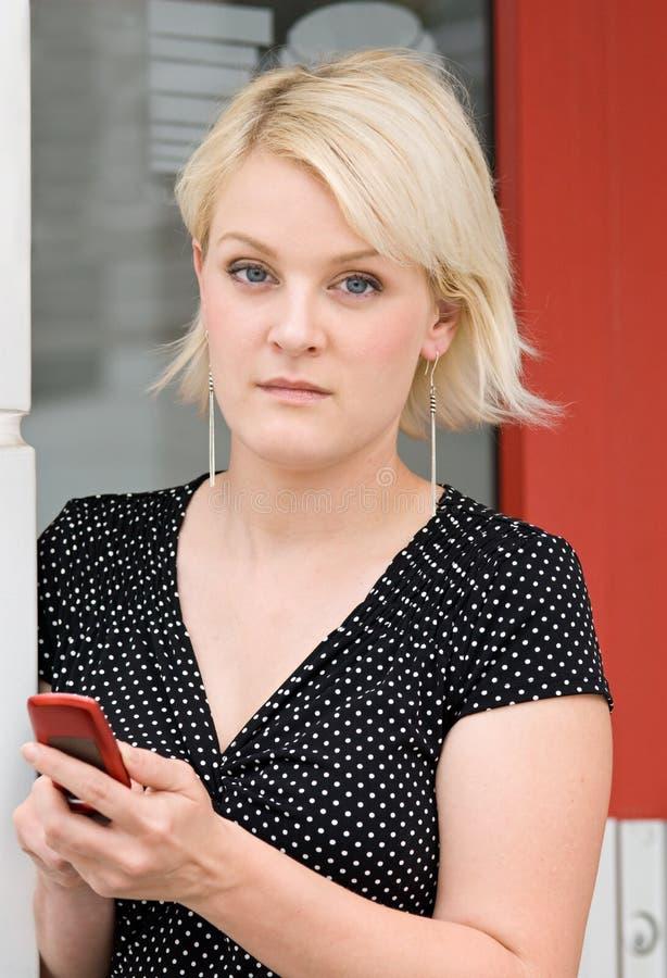 Blond sérieux avec le téléphone images libres de droits