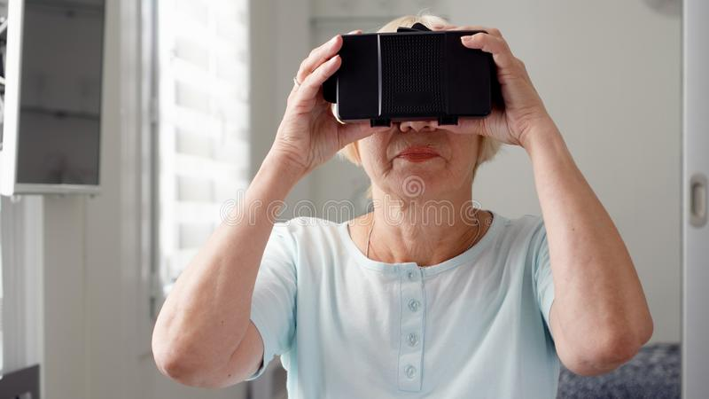 Blond senior woman in white using VR 360 glasses at home. Concept of active modern elderly people royalty free stock photos