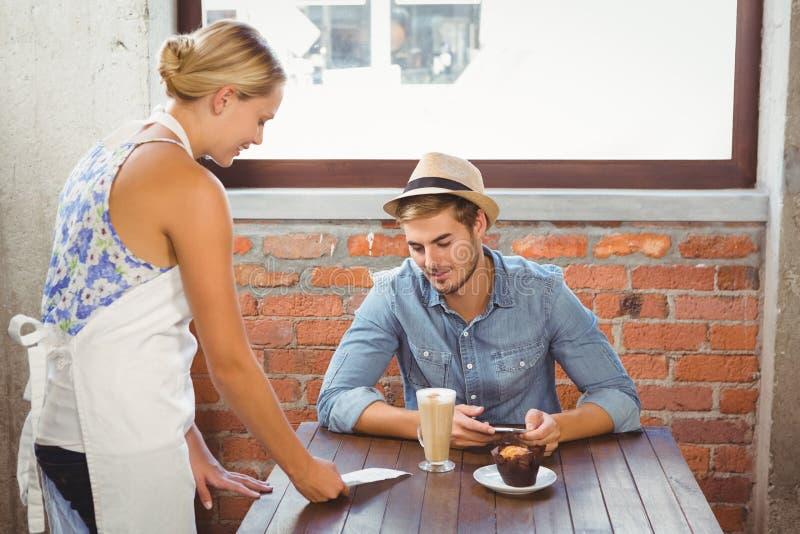 Blond servitrisvisningräkning till den stiliga hipsteren royaltyfri fotografi