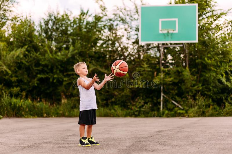 A blond seven-year-old boy in a basketball uniform throws a ball on an open basketball court in the summer. Children and sports. Training stock image